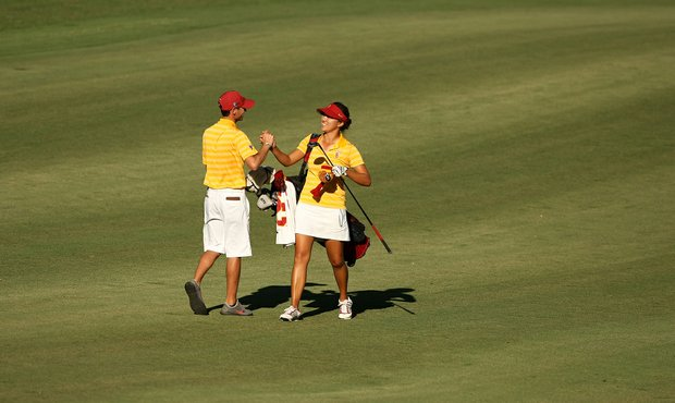 USC's Annie Park and assistant coach Justin Silverstein celebrate in the fairway at No. 18.