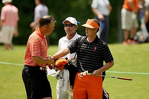 Oklahoma State assistant coach Brian Guetz shakes hands with his player Ian Davis, head coach Mike McGraw is in the background during the final round of stroke play of the 2013 NCAA Championship.