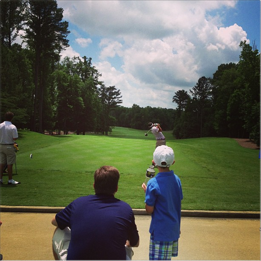 A dad and son watch Alabama's Cory Whitsett hit his tee ball on the par-4 8th hole at Capital City Club.