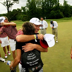 Alabama head coach Jay Seawell gets a hug from Jani Thomas, Justin Thomas' mom at the 2013 NCAA Championship at Capital City Club Crabapple Course.