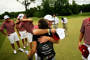Alabama head coach Jay Seawell gets a hug from Jani Thomas, Justin Thomas' mom at the 2013 NCAA Championship at Capital City Club Crabapple Course.