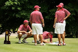 Alabama's Scott Strohmeyer, left, and Cory Whitsett, on the ground sign flags while assistant coach Rob Bradley, Justin Thomas and Bobby Wyatt talks at the 2013 NCAA Championship at Capital City Club Crabapple Course.