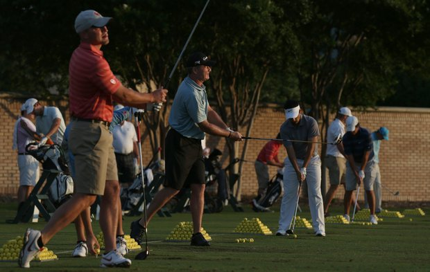 Players warm up on the practice tee at Lakewood Country Club.