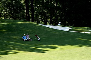 Jay McLuen, right, of Forsyth, G.A. and his caddie sit in the shade at No. 18 during U. S. Open Sectional Qualifying at Hawks Ridge Golf Club in Ball Ground, GA.