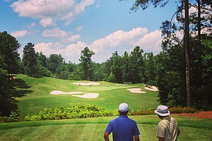 A view from behind No. 5 as Scott Wolfes and his caddie discuss the shot during U. S. Open Sectional Qualifying at Hawks Ridge Golf Club in Ball Ground, GA.