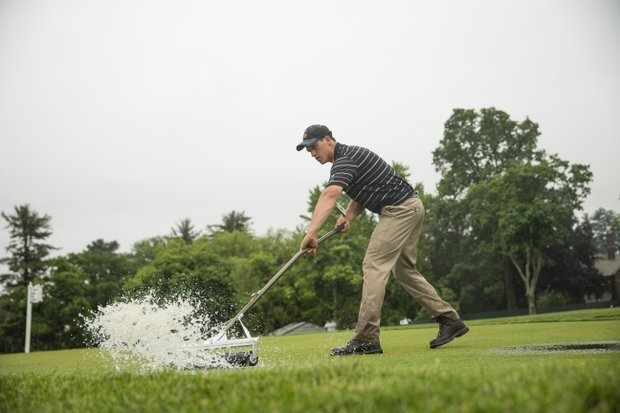 James Bryson, a member of the maintenance staff works to squeegee off standing water at the 15th teeing ground during a practice round at the 2013 U.S. Open at Merion Golf Club in Ardmore, Pa. on Monday, June 10, 2013.