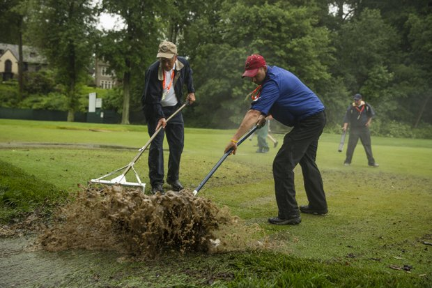 Members of the maintenance staff work to squeegee standing water off the 11th fairway during a practice round at the 2013 U.S. Open at Merion Golf Club in Ardmore, Pa. on Monday, June 10, 2013.