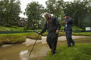 Tim Kelly, a member of the maintenance staff, uses a rake to check the standing water that gathered in a greenside bunker on the 11th hole during a practice round at the 2013 U.S. Open at Merion Golf Club in Ardmore, Pa. on Monday, June 10, 2013.