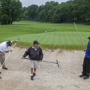 Members of the maintenance staff work to rake a bunker in the practice area during a practice round at the 2013 U.S. Open at Merion Golf Club in Ardmore, Pa. on Monday, June 10, 2013.