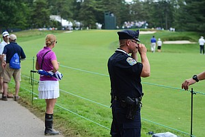 An officer talks to a volunteer while they wait for players to tee off on the 15th hole. The officer is standing out of bounds, only eight feet from the fairway at Merion.