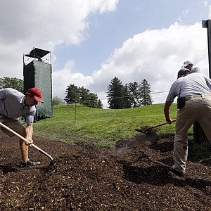 Crews add mulch to a wet walkway as the sun came out for U.S. Open practice Tuesday at Merion GC in Ardmore, Pa.
