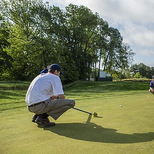 Chris Hartwiger, left, USGA staff, uses the Stimpmeter to measure the speed of the green on the 17th hole as the sun came out for U.S. Open practice Tuesday at Merion GC in Ardmore, Pa.