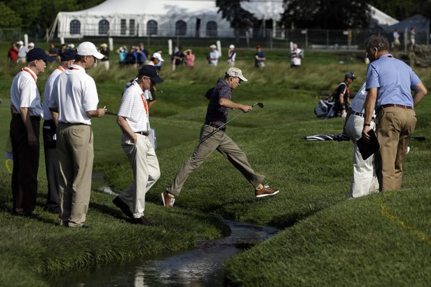 Jim Furyk leaps over a creek as the sun came out for U.S. Open practice Tuesday at Merion GC in Ardmore, Pa.