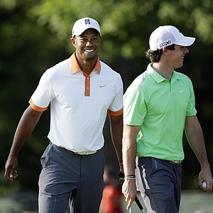 Tiger Woods (left) and Rory McIlroy, smile as they walk the 14th green during practice for the U.S. Open.