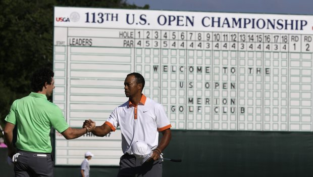 Rory McIlroy (left) and Tiger Woods shake hands after putting on the 18th green during practice for the U.S. Open.
