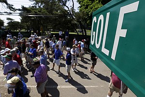 Spectators walk near the first green during practice for the U.S. Open at Merion Golf Club, Wednesday, June 12, 2013, in Ardmore, Pa.