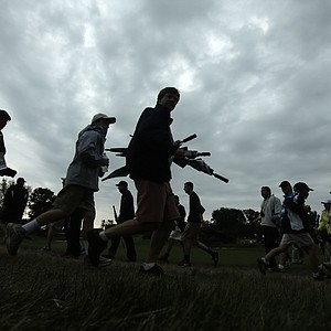 Spectators head of the course as a weather warning delays the first round of the U.S. Open golf tournament at Merion Golf Club, Thursday, June 13, 2013, in Ardmore, Pa.