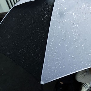A spectator sits under an umbrella as weather delays the first round of the U.S. Open golf tournament at Merion Golf Club, Thursday, June 13, 2013, in Ardmore, Pa.