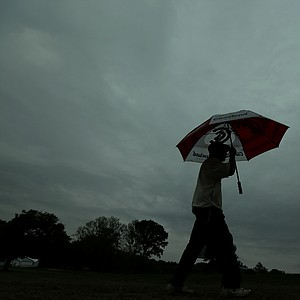 A spectator walks off the course as a weather warning delays the first round of the U.S. Open golf tournament at Merion Golf Club, Thursday, June 13, 2013, in Ardmore, Pa.