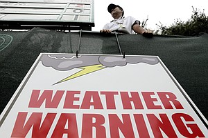 A weather warning sign hangs near the 13th hole during the first round of the U.S. Open golf tournament at Merion Golf Club, Thursday, June 13, 2013, in Ardmore, Pa.