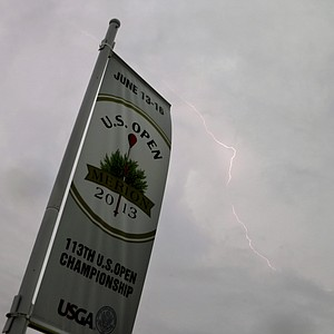 Lightning flashes in the sky as a weather warning delays the first round of the U.S. Open golf tournament at Merion Golf Club, Thursday, June 13, 2013, in Ardmore, Pa.