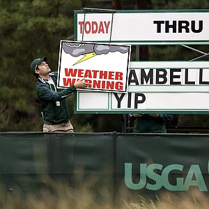 A course worker hangs up a weather warning sign along the fourth hole during the first round of the U.S. Open golf tournament at Merion Golf Club, Thursday, June 13, 2013, in Ardmore, Pa.