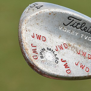 "Webb Simpson's Titleist Vokey Design SM4 sand wedge is covered with ""JWD"" stamps in red."