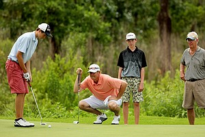 The Olson family look over a putt at No. 14 during the Golfweek Father & Son Open at Reunion Resort.