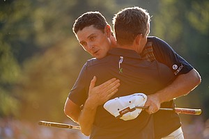 Justin Rose embraces Luke Donald after putting on the 18th hole to complete the final round of the U.S. Open at Merion Golf Club.