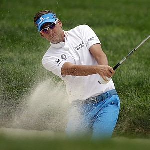 Ian Poulter hits out of a bunker on the first hole during the fourth round of the U.S. Open.