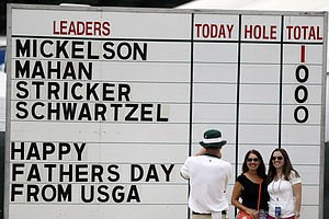 Spectators pose for a photo before the start of the fourth round of the U.S. Open.