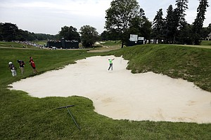Rory McIlroy hits out of a bunker on the third hole during the fourth round of the U.S. Open.