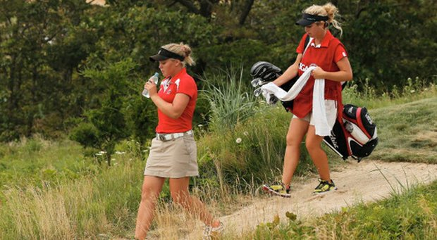 Brooke Mackenzie Henderson of Canada walks with her sister/caddie Brittany during the first round of the 2013 U.S. Women's Open at Sebonack Golf Club.