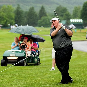 Jim Justice, the owner of Greenbrier Resort, hits his second shot from outside the ropes at No. 17 while playing in a ProAm with Phil Mickelson.