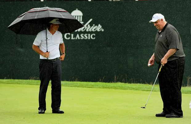 Phil Mickelson watches Jim Justice make his final putt at No. 18 as the rain falls harder.