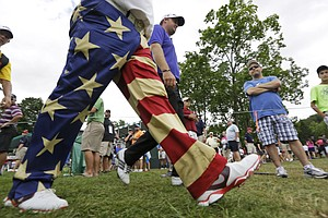 John Daly, front with patriotic pants, walks with fellow golfer, Peter Hanson, right, during the first round of the Greenbrier Classic.