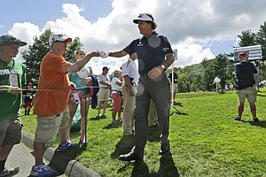 Phil Mickelson gives a fist-bump to a fan as he heads to the 11th tee during the first round of the Greenbrier Classic.