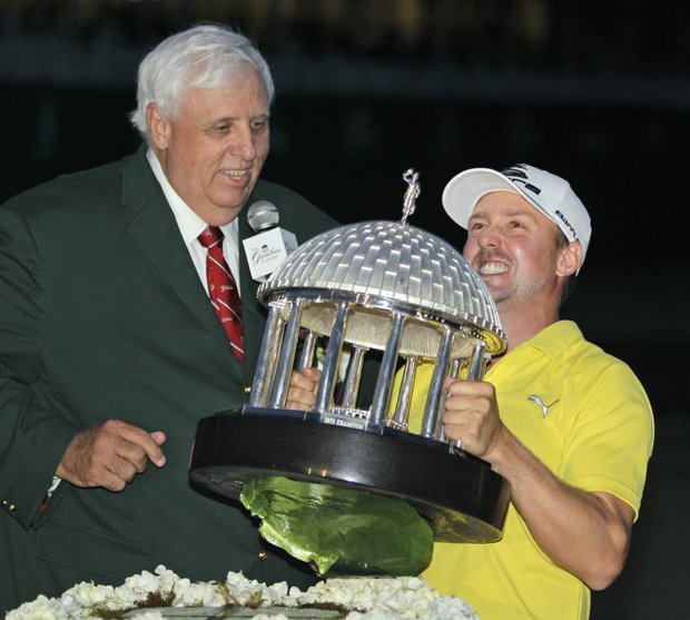 Jonas Blixt struggles to lift the trophy as Greenbrier resort owner Jim Justice, left, watches after Blixt won the Greenbrier Classic.