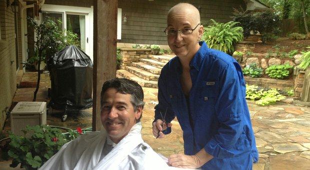 Auburn coach Kim Evans prepares to cut and shave Vanderbilt coach Greg Allen's hair. Allen is showing his support for Evans' fight against ovarian cancer.