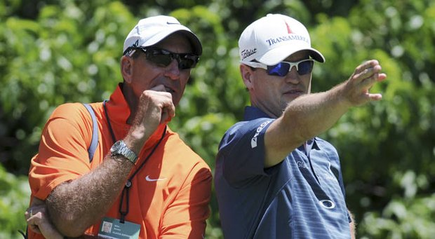 John Deere Classic defending champion Zach Johnson, right, confers with his swing coach, Mike Bender, before teeing off on the second hole during the pro-am for the golf tournament Wednesday, July 10, 2013, in Silvis, Ill.