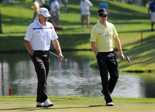 Steve Stricker, left, and Zach Johnson walk on the 18th green during the John Deere Classic.