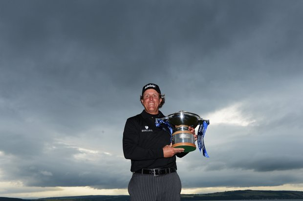 Phil Mickelson poses with the trophy after his victory on the first hole of a sudden-death playoff during the final round of the Scottish Open at Castle Stuart.