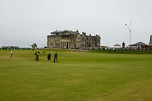 Gofers playing the 18th hole with the R&A Clubhouse in the background at St. Andrews.