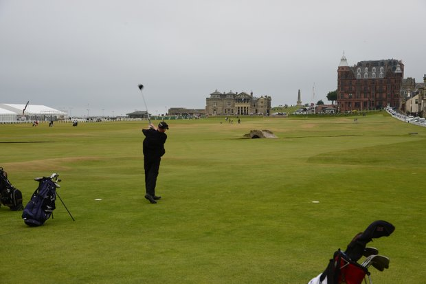 Golfer teeing off the 18th hole with R&A Clubhouse and Hamilton Hall in the background at St. Andrews.