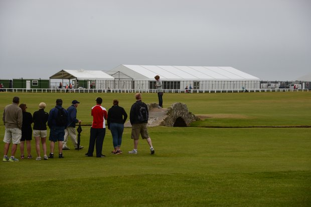 A line for fans to get their picture taken on the Swilican Bridge between golfers teeing off the 18th tee at St. Andrews.