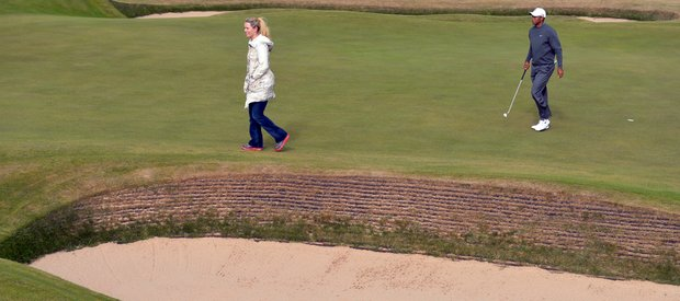 Tiger Woods walks across the18th green with his girlfriend, Lindsey Vonn, during a practice session ahead of the Open Championship at Muirfield.
