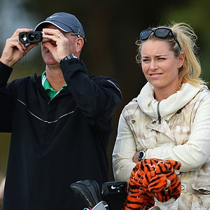 Tiger Woods' caddie Joe LaCava stands with skier Lindsey Vonn as they watch Woods during a practice round ahead of the Open Championship at Muirfield.