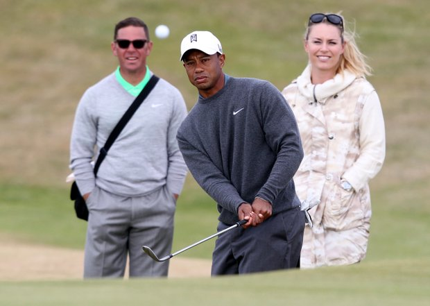 Tiger Woods plays a shot as his girlfriend, Lindsey Vonn, and his coach Sean Foley look on during a practice round for the 2013 Open Championship at Muirfield.