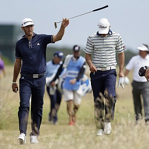 Brooks Koepka, center, walks with Dustin Johnson to the 17th tee during a practice round Tuesday ahead of the Open Championship at Muirfield.