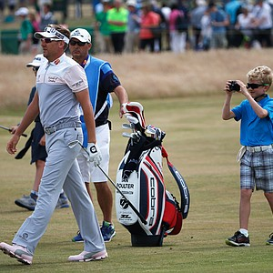 Ian Poulter walks in front of son Luke who is taking pictures ahead of the 142nd Open Championship at Muirfield.